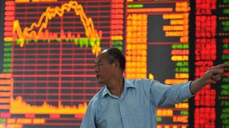 An investor watches the electronic board at a stock exchange hall in Fuyang, China.